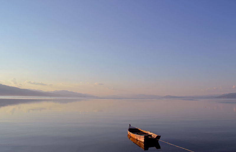 Boat moored in river against clear sky during sunset