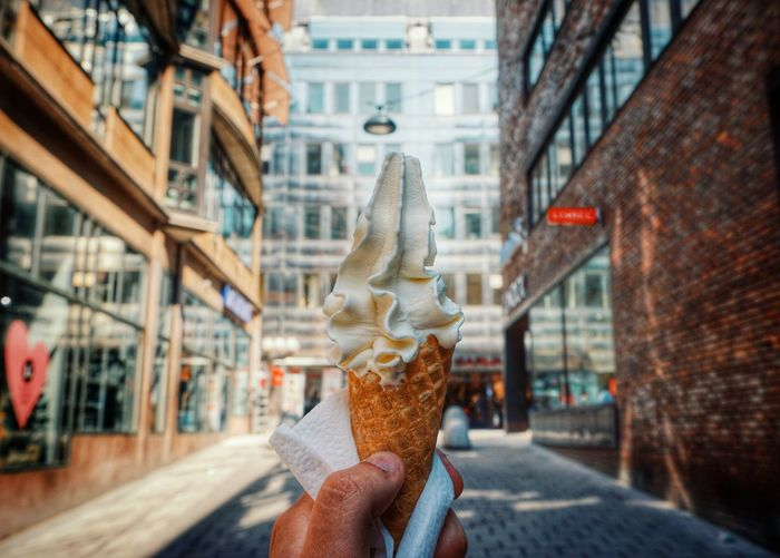 Midsection of person holding ice cream against building in city