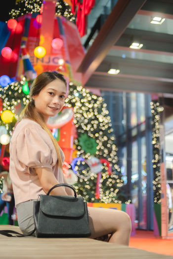 Portrait of young woman with christmas tree at home