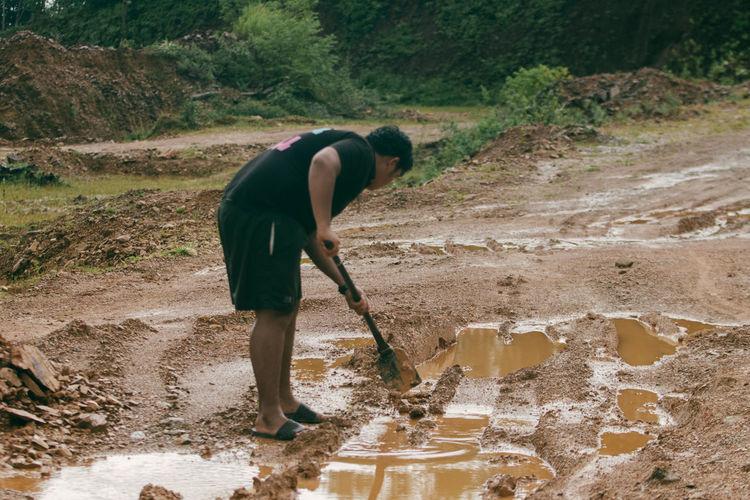 Full length of man working on dirt road