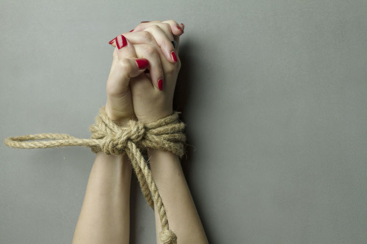 Close-up of hands tied with rope on gray background