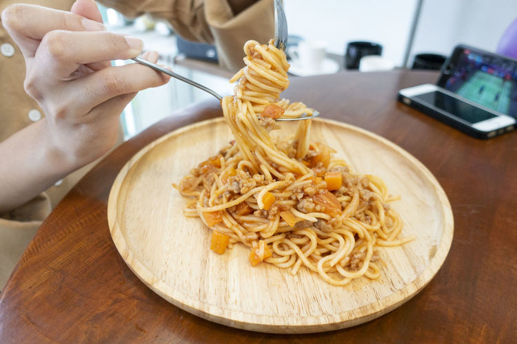 Midsection of woman with noodles in plate on table