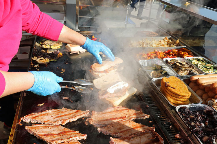 High angle view of people preparing food on barbecue grill