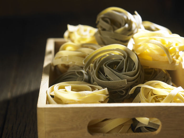 close up tagliatelle pasta Container Food And Drink Spaghetti Tagliatelle Wheat Wood Grain Carbohydrate - Food Type Close-up Crate Directly Above Fettuccine Food Freshness Healthy Eating High Angle View Indoors  Ingredient Italian Food No People Pasta Raw Food Still Life Table Wood - Material Yellow