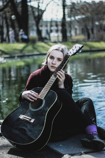 Portrait of young woman playing guitar in lake