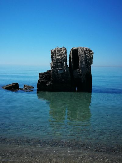Built Structure On Rocks By Sea Against Clear Blue Sky