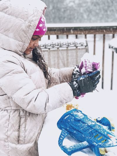 Girl In Warm Clothing Holding Bottle During Snowfall