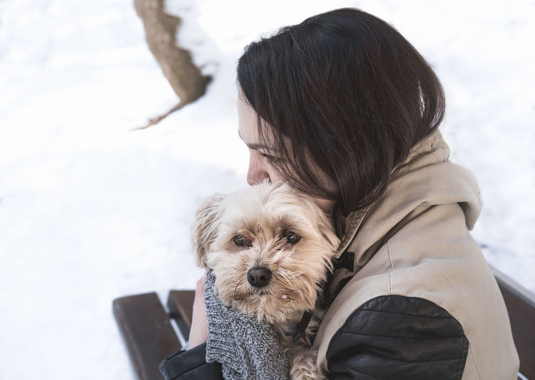 Close-up of woman holding dog on snow covered field