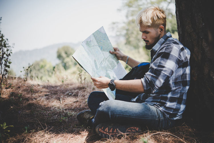 Side View Of Man Reading Map While Sitting By Tree On Field