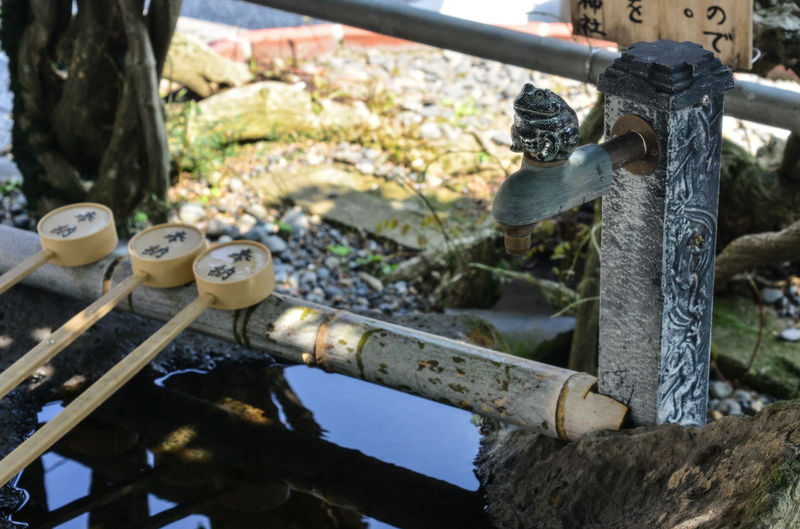 Close-up of water fountain with bamboo ladles