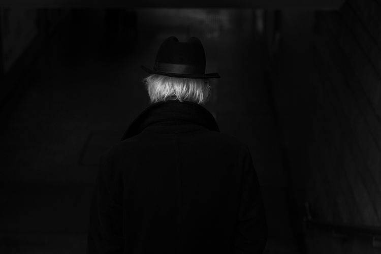Rear view of man wearing hat walking in subway