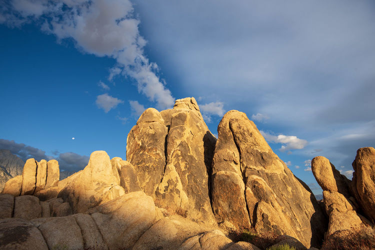 Morning sunshine on desert rock formations with white clouds in blue sky