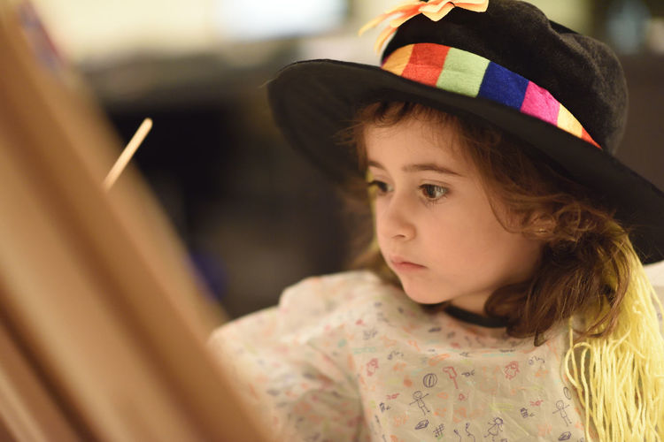 Close-Up Of Cute Girl Wearing Hat While Painting
