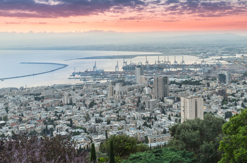 Haifa, Israel, June 30, 2018 : Dawn in Haifa. View of the Downtown Haifa and Haifa Bay from Mount Carmel. Architecture Bahai Gardens Beautiful City Cityscape Downtown Haifa Israel Haifa Bay Harbor Mediterranean Sea Modern Tree View Building Down Hill Landmark Mount Carmel Scenics Sky Street Tourism Town Travel Destinations Urban