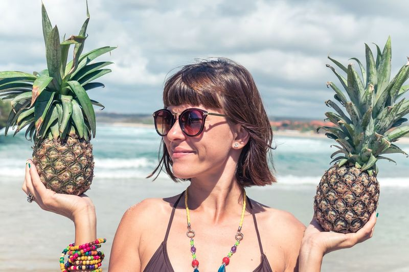 Smiling Young Woman Holding Pineapples At Beach