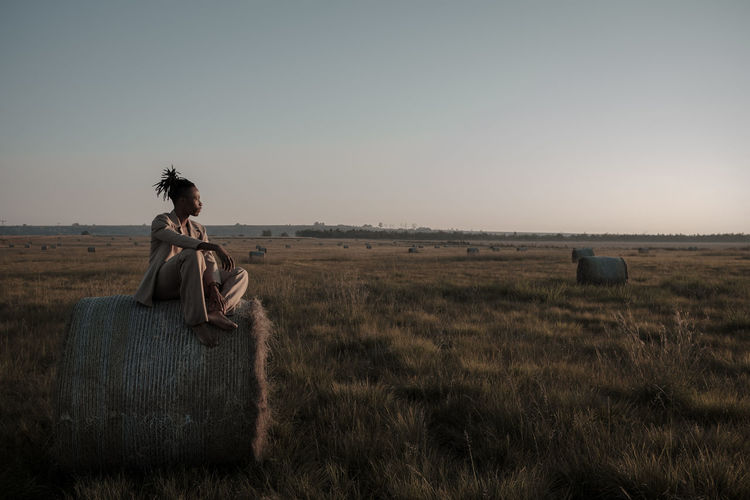 Young man sitting on hay bale at agricultural landscape