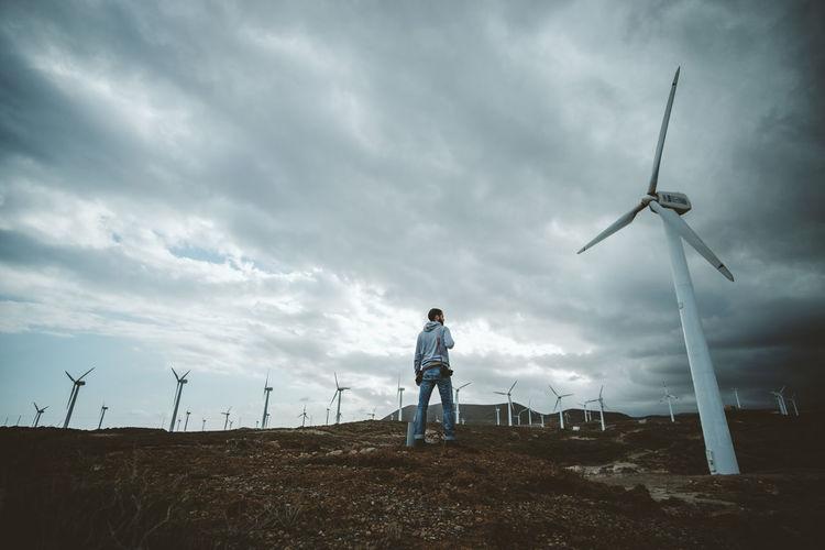 Man standing on field against wind turbines