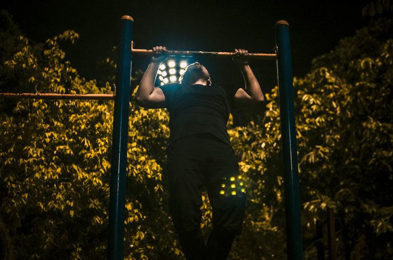 Man practicing chin-ups on gymnastic bars against trees at public park during night