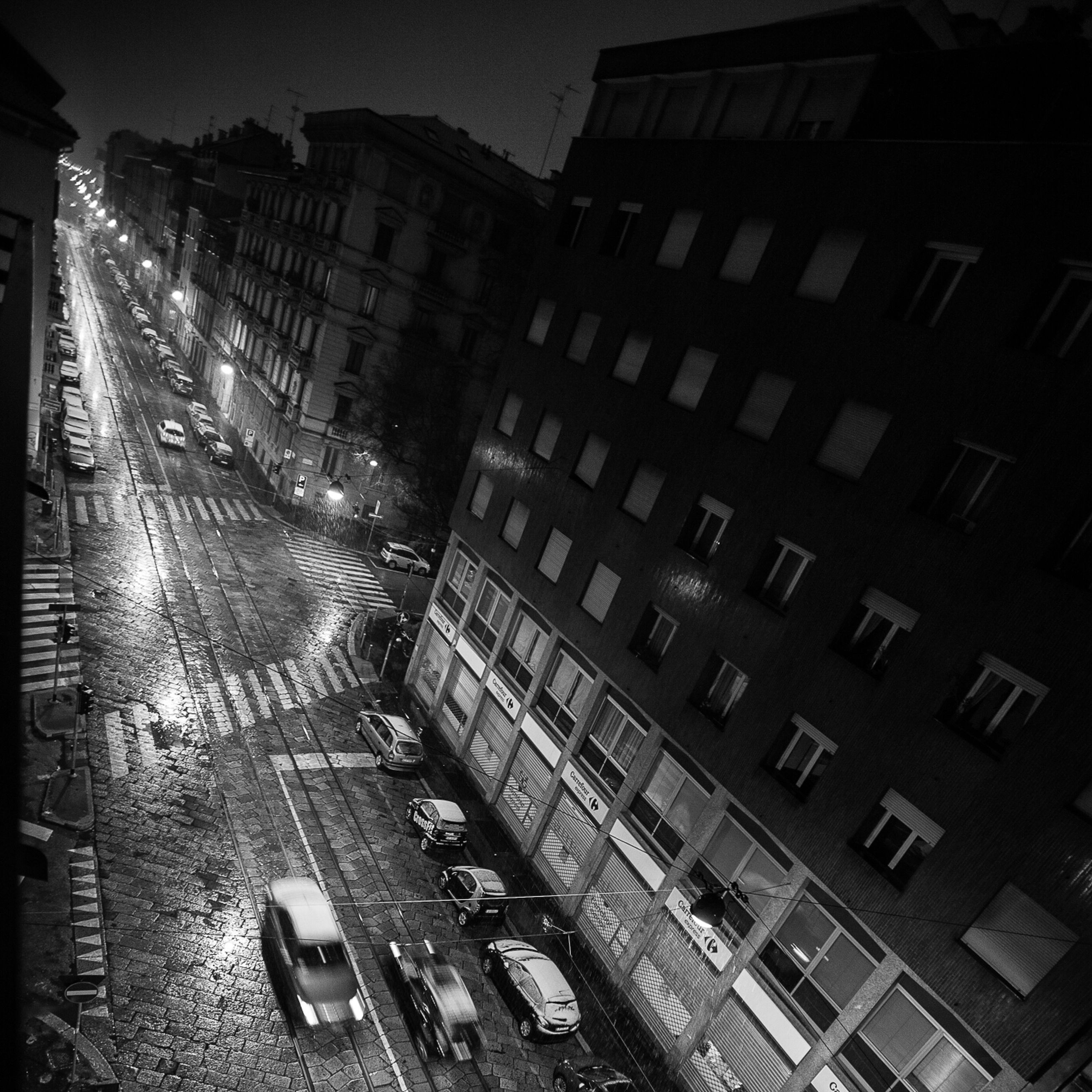 building exterior, architecture, built structure, city, building, illuminated, residential building, night, street, city life, window, residential structure, office building, high angle view, outdoors, low angle view, city street, no people, modern, street light