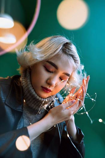 Close-up of woman holding illuminated lights