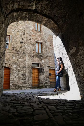 Woman Standing Below Arch In City