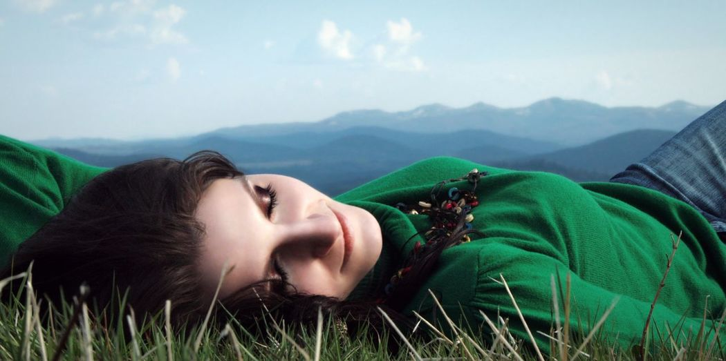 Smiling beautiful woman lying on field by mountains against sky