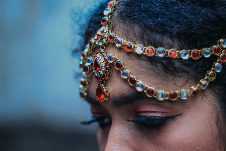 Close-up of woman wearing make-up and jewelry