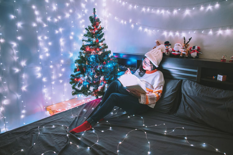 Christmas lights instantly make me feel eight years old again.❄🎅🎄 Young woman reading a lamp book in a room with the Christmas tree. Night Lights Nightphotography Light Vintage Nightlife Women Light And Shadow Portrait Room New York Happiness Holiday Night Lights Celebration Lighthouse Christmas Night Photography Christmas Lights Christmas Decoration New Year Lifestyles Lighting Equipment Christmas Ornament Capture Tomorrow