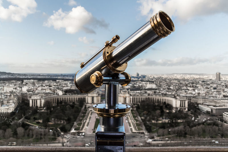 Close-up of hand-held telescope in city against sky