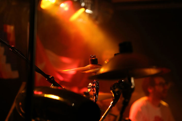 Close-up of drum kit with man in background at of music concert