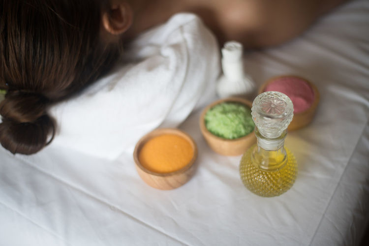 Young woman lying by spa products on massage table