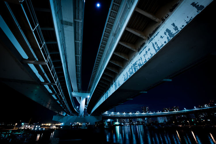Illuminated bridge in city against sky at night