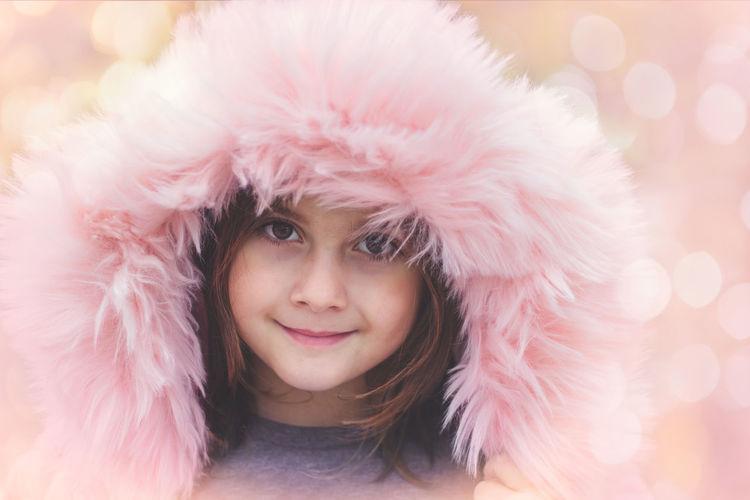 Close-Up Portrait Of Smiling Girl Wearing Pink Fur Coat