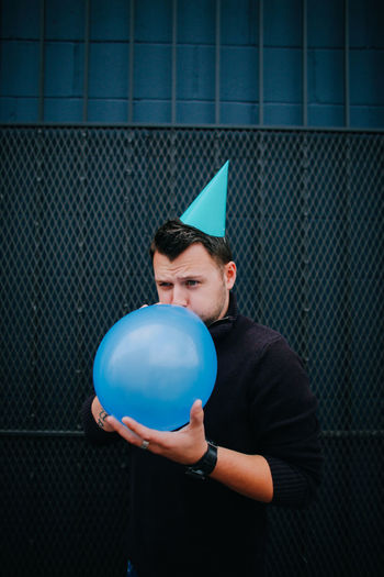 Man wearing party hat blowing balloon against metal grate