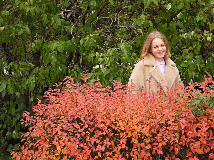 Portrait of a smiling young woman by plants