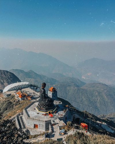 High angle view of buddha statue on mountain against sky