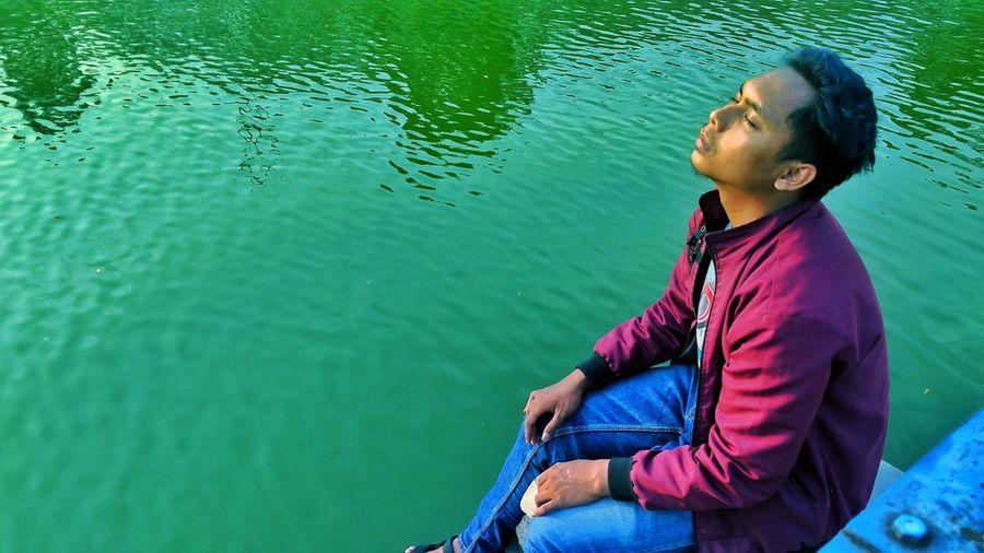 Side view of man sitting in lake