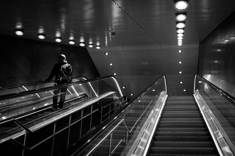 Man on escalator at illuminated railroad station