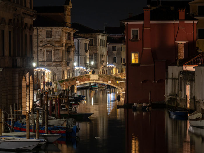 Sailboats moored in canal amidst buildings in city at night