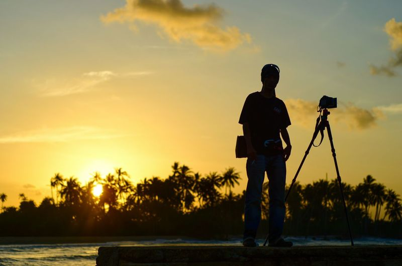 Scenic view of photographer silhoutte on the sunset background. Silhouette Photographer Tripod Wallpaper Amazing Scenics Backgrounds Sunset Beach Sunrise Camera DSLR Malaysia