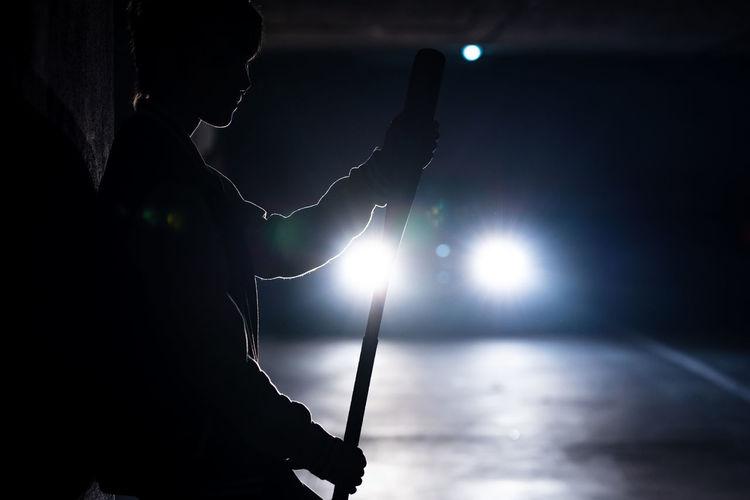Silhouette man playing illuminated at night