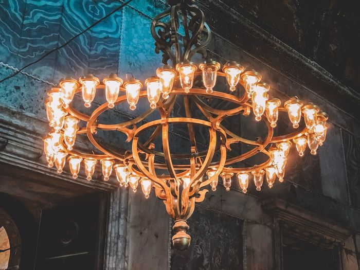 Low angle view of illuminated chandelier against building
