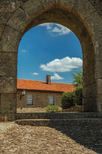 Old building against sky seen through arch window