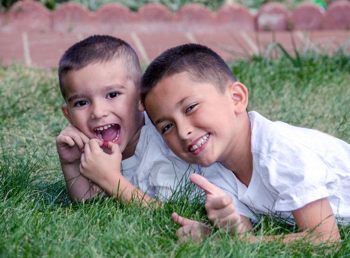 Portrait of happy friends lying on grass