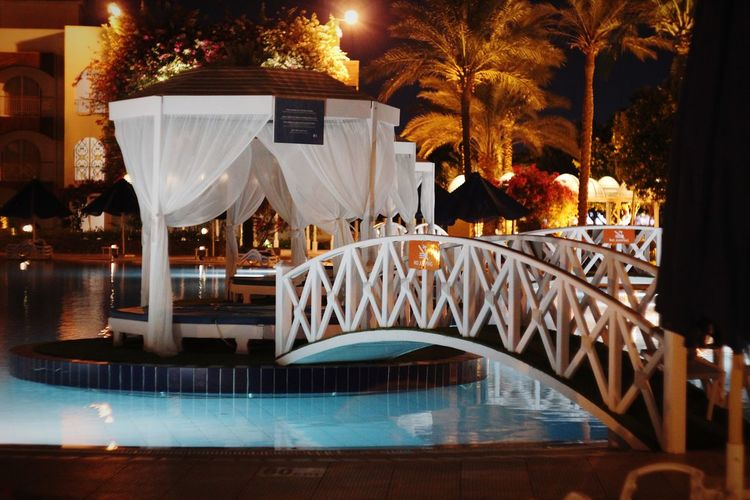 Chairs and tables by swimming pool at night