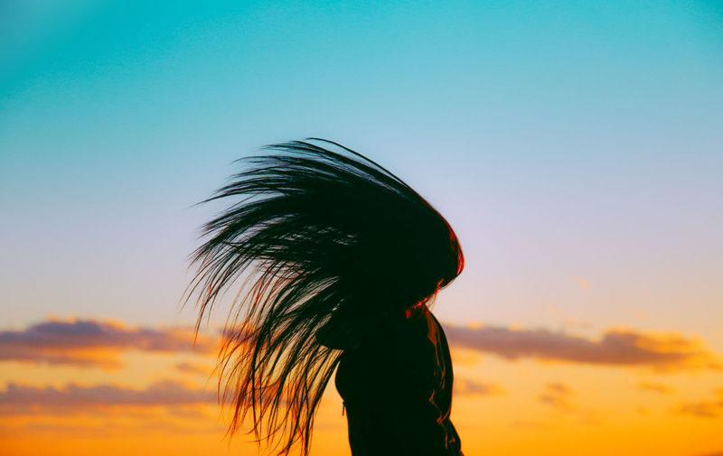 Silhouette Woman Tossing Hair Against Sky During Sunset