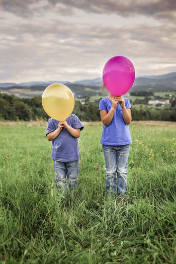 Rear view of people with balloons standing on field against sky