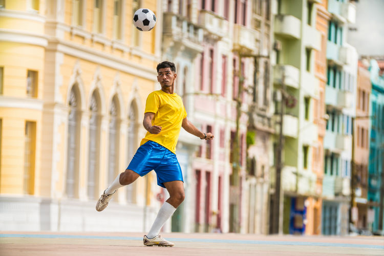 Soccer player kicking ball in the city 2018 Brazil City Determination Football Skill  Soccer Game Brazilian Buildings Day Expertise Kicking Motion Player Playing Soccer Soccer Ball Soccer Goal Soccer Life Soccer Player Soccer Shoe Soccer Uniform Soccer⚽ Sport Sucess