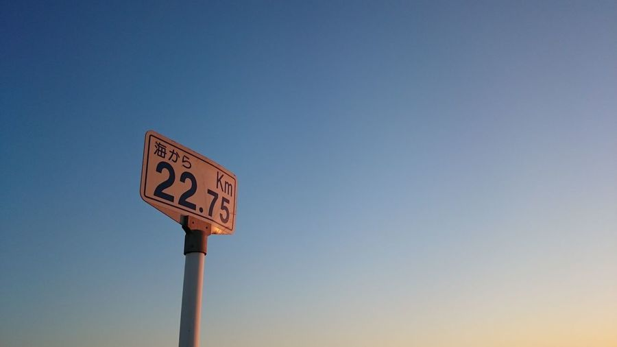 Low Angle View Of Distance Marker Against Clear Sky