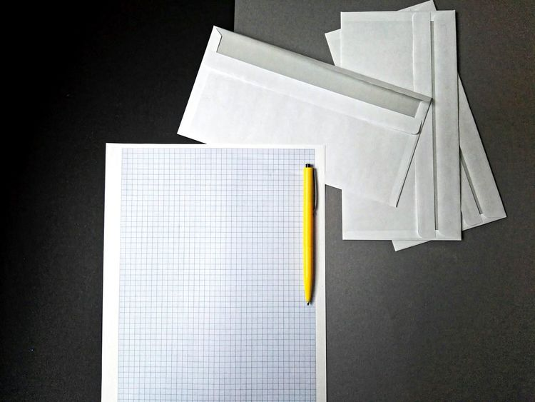 Lets write something Paper No People Business Finance And Industry Close-up Black Background Sheet Of Paper Envelopes Yellow Pen Buisness Empty Paper Desk From Above